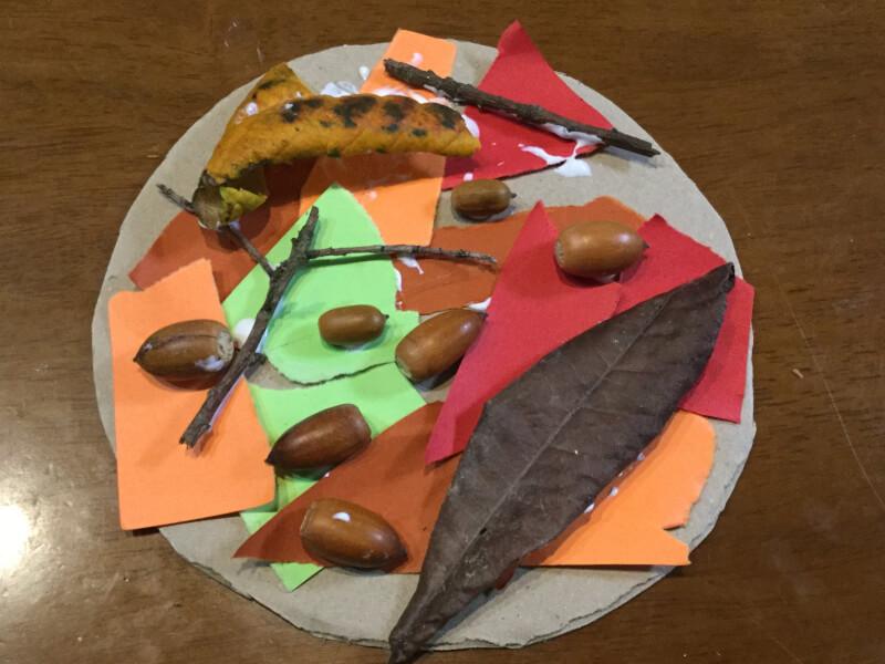秋の製作でドングリや枝などを貼り付けている写真